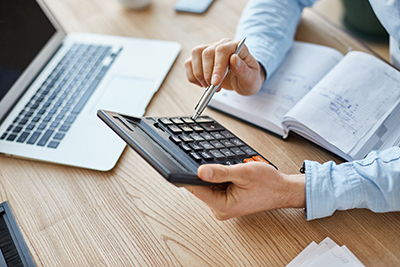 Cropped view of professional serious finance manager, holding calculator in hands, checking company month's profits, looking through details on laptop, writing down information for meeting with director